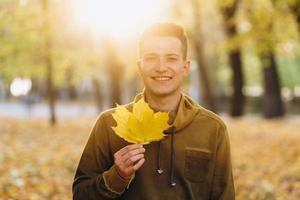 chico sonriendo y sosteniendo un ramo de hojas de otoño en el parque foto
