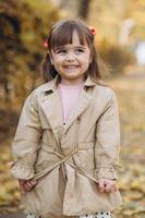 Beautiful little girl in a beige coat walks in the autumn park photo