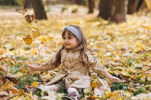 Little girl in a beige coat sitting among leaves in the autumn park. photo
