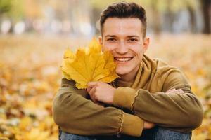 niño con un ramo de hojas sonriendo y soñando en el parque de otoño foto