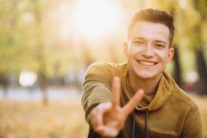 chico guapo sonriendo y mostrando paz en el parque de otoño foto