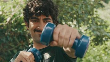 Man standing in garden making boxing movements with dumbbells video