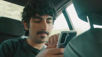 Mann sitzt hinten im Auto, tippt auf dem Smartphone und schaut sich um video