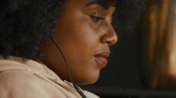 Close up of woman with earphones sitting and watching smartphone video
