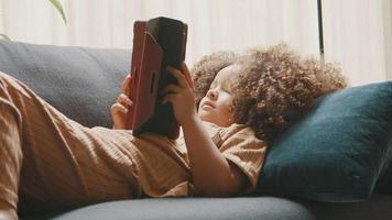 Girl lying on couch watching tablet video
