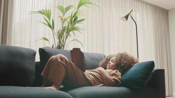 flicka som ligger på soffan och tittar på surfplattan video