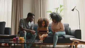 man och kvinna på soffan tittar på flicka med surfplatta video