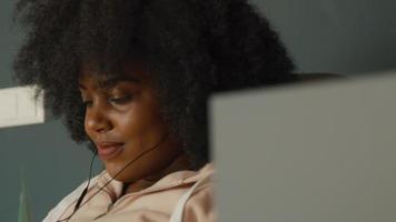 vrouw met koptelefoon zittend beweegt op muziek en kijkt op video