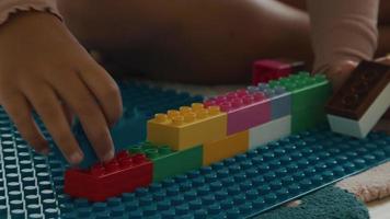 närbild av byggstenar byggda av tjejen som tittar upp och pratar video