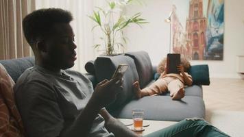 man sitter med smartphone och flicka som ligger på soffan och tittar på surfplattan video