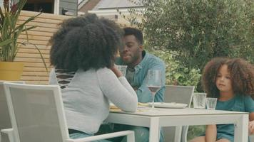 kvinna man och flicka sitter i trädgården och pratar vid bordet efter maten video