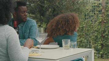 Mujer, hombre y niña sentados para comer en la terraza levantando copas video