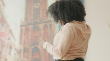 Woman with earphones and smartphone walks in living room video