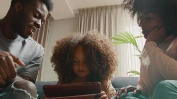 man och kvinna på soffan pratar med tjejen som tittar på surfplattan video