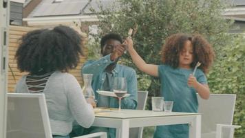 kvinna man och flicka städa upp bord i trädgården efter måltid video