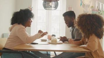 flicka och man sitter vid bordet och tittar på kvinnan som skär födelsedagstårta video