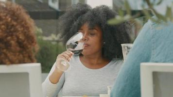 Mujer prueba el vino mientras está sentado a la mesa en la terraza con una niña y un hombre video