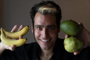 el hombre sonríe y sostiene la fruta cerca. promueve alimentos crudos saludables foto