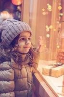 Little girl infront of window of a store, full of wrapped gifts photo