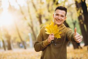 Guy smiling and holding a bouquet of autumn leaves in the park photo