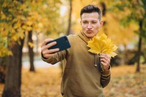 Guy holding a bouquet of leaves and taking selfie with kiss in park photo