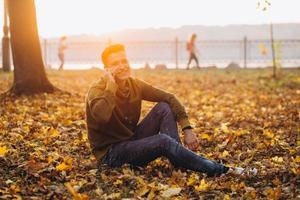 Happy guy smiling and talking on the phone in the autumn park photo