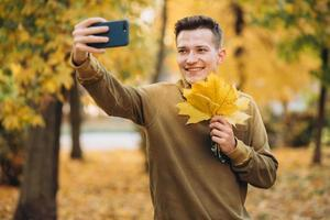 Guy smiling and holding a bouquet of leaves and taking selfie in park photo
