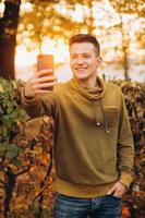 Chico sonriendo y sosteniendo un ramo de hojas y tomando selfie en el parque foto