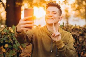 chico sosteniendo un ramo de hojas de otoño y tomando un selfie en el parque foto