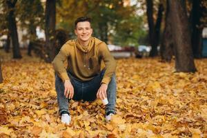 Handsome and happy boy smiling and dreaming in the autumn park photo