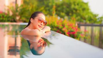 Young woman enjoys around outdoor swimming pool video