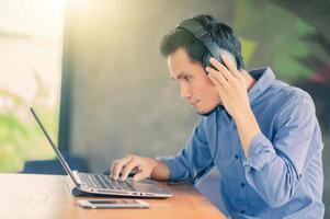 Man working computer listening music at cafe ,Freelancer work at cafe photo