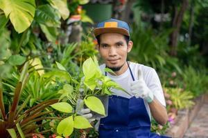 Hombre asiático feliz vender jardín de plantas en la tienda foto