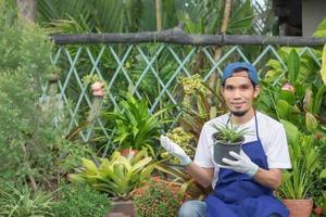 El hombre vende jardín de plantas en la tienda foto