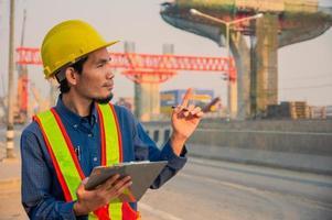 Casco de ingeniero trabaja duro desarrollo en la construcción del sitio foto