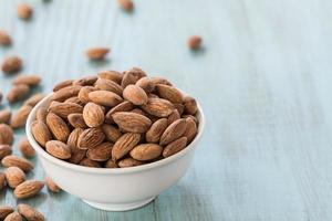 Almonds In White Bowl and Scattered on Blue Wood Background photo