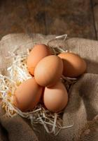 fresh Organic eggs in burlap with dry grass on wood table photo