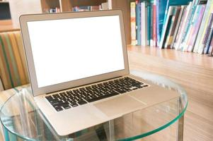Laptop with blank screen on wooden table in front of library photo
