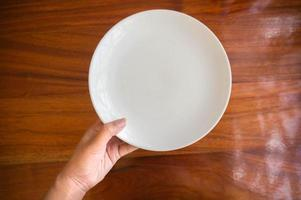 Female hands hold a white dish plate photo