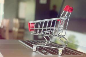 Pequeño carrito de compras con computadora portátil para compras en línea concepto foto