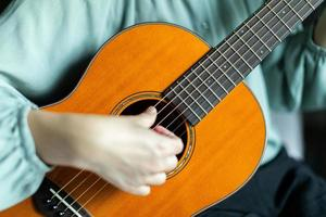 Woman strumming strings of wooden solid acoustic guitar. photo