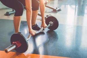 Close up of sports woman lifting weight in fitness gym photo