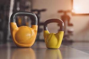 Kettlebells or dumbbells on fitness gym floor photo