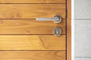 manija de la puerta de acero inoxidable y puerta de madera foto