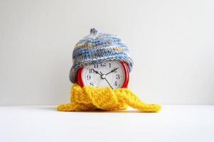 Despertador redondo rojo con gorro azul de lana tejida y pañuelo amarillo sobre un fondo blanco. concepto de invierno. temporada de invierno. acogedor y cálido. tiempo analógico 10 10. espacio para texto. bandera foto