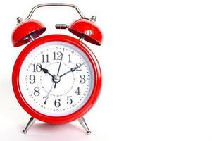 Despertador analógico redondo rojo aislado sobre fondo blanco. tiempo 10 10 foto
