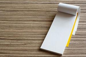 Blank page of writing pad on wooden background photo