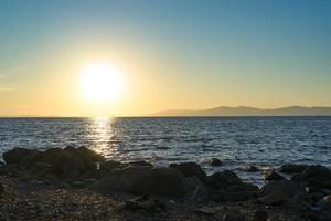 paisaje marino con hermosa puesta de sol y barcos foto