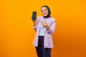 Joven mujer asiática apuntando con alegría en el teléfono inteligente con su dedo foto