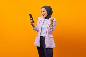 Mujer mostrando la pantalla en blanco del teléfono inteligente y celebrando el éxito foto